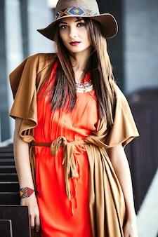Lustige stilvolle sexy lächelnde schöne junge hippie-frau modell im sommer helle hipster kleidung kleid in der straße in hut