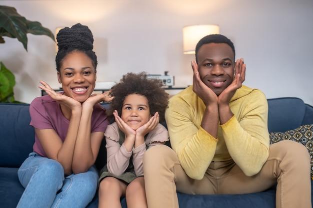 Lustige stimmung. afroamerikaner mann frau und kleines mädchen mit palmen in der nähe des kinns fröhliches sitzen auf dem sofa zu hause
