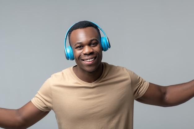 Lustige stimmung. freudiger junger erwachsener afroamerikaner in den kabellosen kopfhörern, die händchenhalten an den seiten im studio stehen