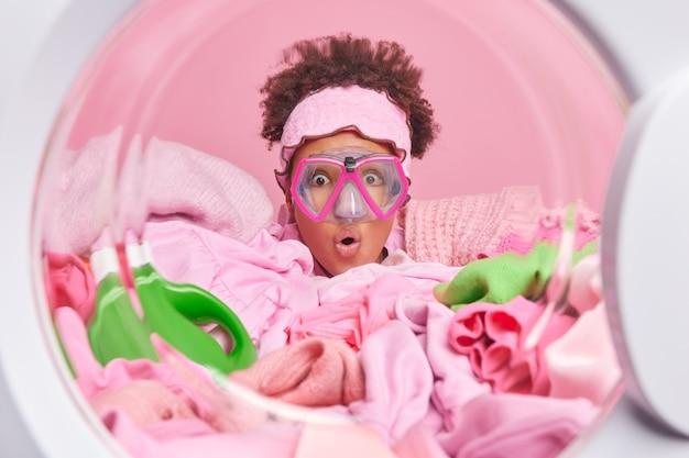 Lustige überraschte weibliche hausfrau mit lockigem haar trägt schnorchelmaskenposen im waschmaschinenkreis mit wäsche und waschmittel herum