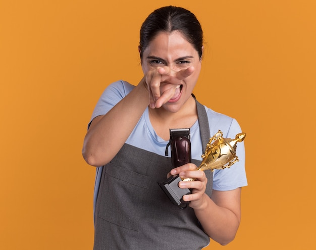 Lustige und freudige junge schöne friseurin in der schürze, die trimmer und goldtrophäe hält, die mit den fingern an der spitze stehen, die über orange wand stehen