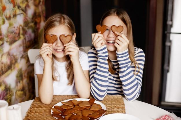 Lustige und lachende mädchen halten herzförmige kekse, schließen die augen und spielen herum