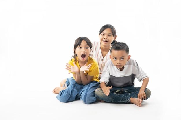 Lustige und nette gruppe asiatische schauende kinder und überraschung