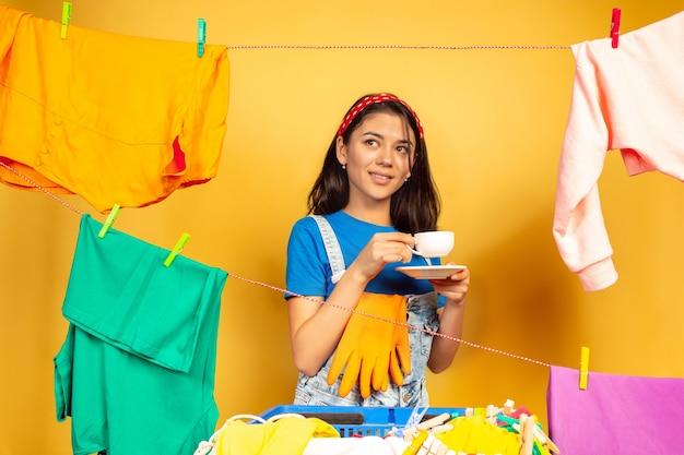 Lustige und schöne hausfrau, die hausarbeit auf gelbem hintergrund tut