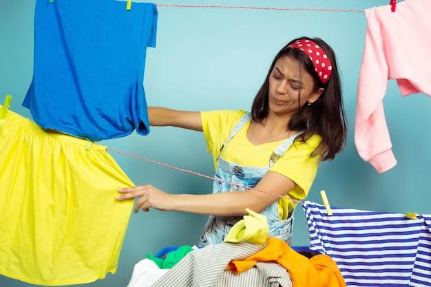 Lustige und schöne hausfrau, die hausarbeit lokalisiert auf blauem hintergrund tut. junge kaukasische frau, die durch gewaschene kleidung umgeben ist. häusliches leben, helle kunstwerke, haushaltskonzept. wäsche falten.