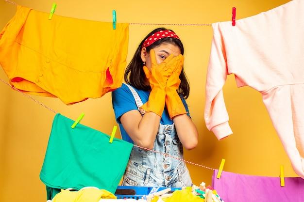 Lustige und schöne hausfrau, die hausarbeit lokalisiert auf gelbem hintergrund tut. junge kaukasische frau, die durch gewaschene kleidung umgeben ist. häusliches leben, helle kunstwerke, haushaltskonzept. erschrocken.