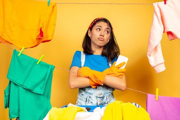 Lustige und schöne hausfrau, die hausarbeit lokalisiert auf gelbem hintergrund tut. junge kaukasische frau, die durch gewaschene kleidung umgeben ist. häusliches leben, helle kunstwerke, haushaltskonzept. hände gekreuzt.