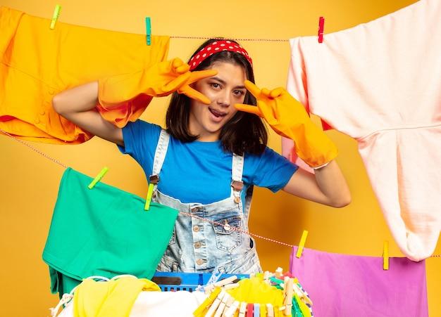 Lustige und schöne hausfrau, die hausarbeit lokalisiert auf gelbem hintergrund tut. junge kaukasische frau, die durch gewaschene kleidung umgeben ist. häusliches leben, helle kunstwerke, haushaltskonzept. posieren, lächelt.