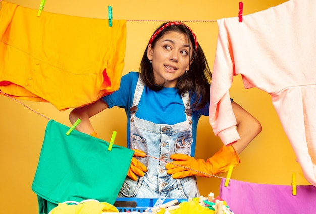 Lustige und schöne hausfrau, die hausarbeit lokalisiert auf gelbem raum tut. junge kaukasische frau, die durch gewaschene kleidung umgeben ist