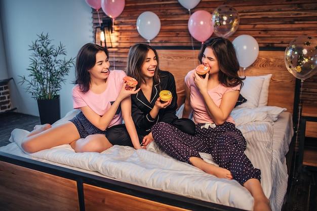 Lustige und verspielte junge frauen sitzen auf dem bett im festlichen raum. mädchen am rechten biss donut. weitere zwei geben ihr ihre donuts. alle frauen lächeln. sie sehen glücklich aus.
