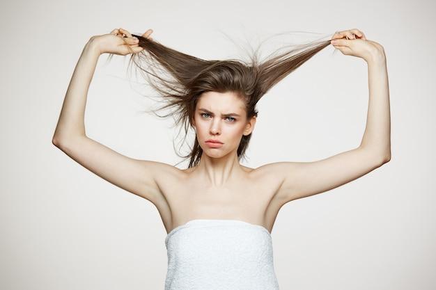 Lustige unzufriedene junge frau im handtuch, das haare berührt. beauty spa und kosmetikkonzept.