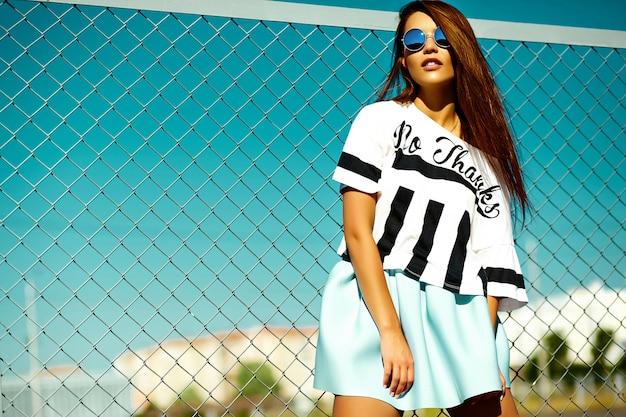 Lustige verrückte glamouröse stilvolle sexy lächelnde schöne junge frau modell in hellen hipster sommer freizeitkleidung in der straße hinter blauem himmel