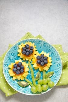 Lustige waffel-sonnenblumen mit kiwi, traube, pfirsichen und blaubeeren