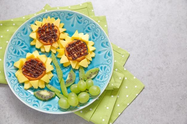 Lustige waffel-sonnenblumen mit kiwi, traube und pfirsichen