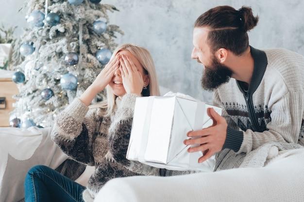 Lustige weihnachtsfeier. guy bereitete ein überraschungsgeschenk für seine freundin vor. lady aufgeregt über das geschenk, bedeckte die augen und lächelte.