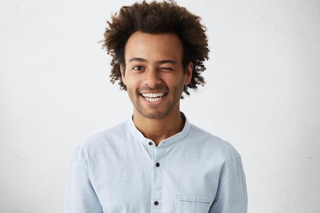 Lustiger afrikanischer mann mit buschigem lockigem haar, das sein auge mit warmem breitem lächeln blinzelt