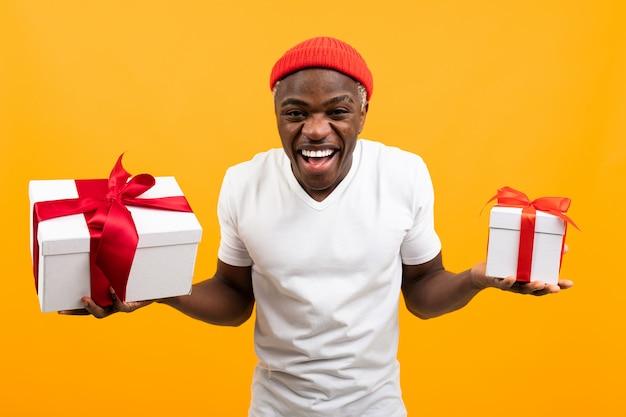 Lustiger afrikanischer mann mit einem lächeln in einem weißen t-shirt hält zwei kisten ein geschenk mit einem roten band für valentinstag auf einem gelben studiohintergrund