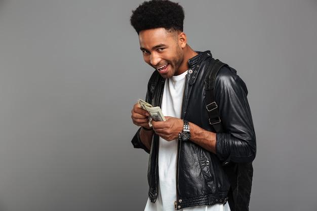 Lustiger afrikanischer mann mit stilvollem haarschnitt betrachtet gierig das geld und schaut