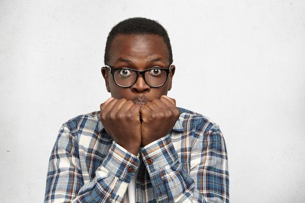 Lustiger afroamerikanischer student mit pop-augen in brillen, der sich vor den prüfungen am college nervös und ängstlich fühlt und die hände in den fäusten vor seinem gesicht hält. schwarzer mann, der ängstlich und mit etwas erschrocken aussieht