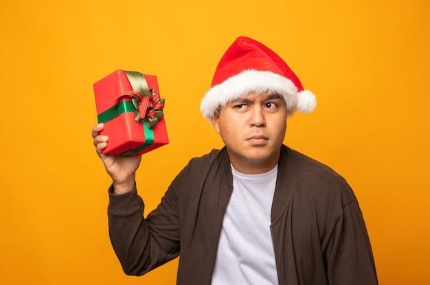 Lustiger asiatischer mann, der die geschenkbox schüttelt, die er wissen möchte, was ding in der box ist.