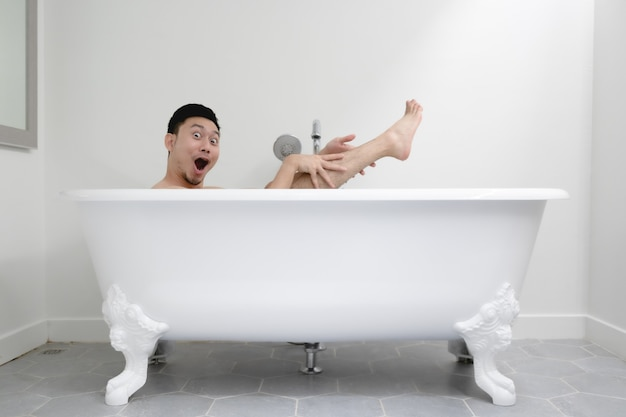 Lustiger asiatischer mann, der versucht, in der weißen badewanne sexy zu sein. konzept von spaß und entspannung.
