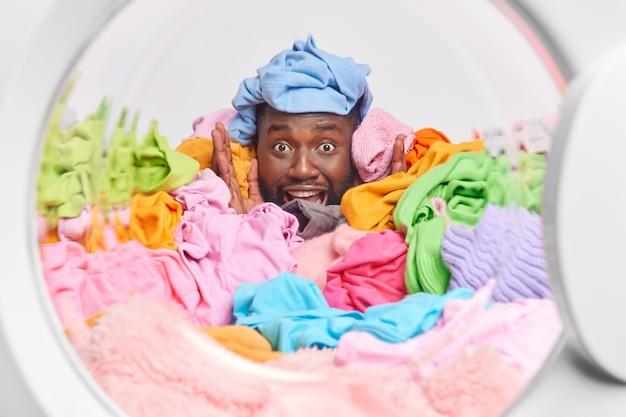 Lustiger bärtiger afro-amerikaner, der mit bunten kleidern bedeckt ist, die zum waschen von posen aus der waschmaschine gesammelt wurden, lächelt breit