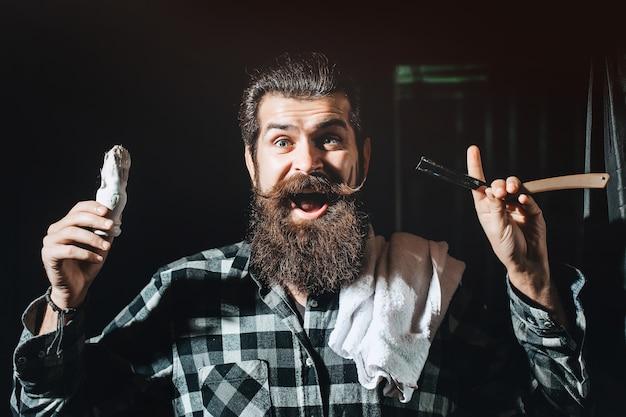 Lustiger bärtiger friseur mit schere und rasiermesser im friseursalon vintage friseursalon rasierporträt bärtiger mann schnurrbart männer brutaler kerl schere rasiermesser