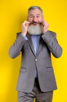 Lustiger bärtiger gutaussehender mann des studioporträts im grauen geschäftsanzug, der kamera, arbeitsberufslebensstil, gelben hintergrund sucht.