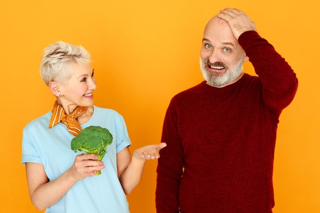 Lustiger bärtiger männlicher rentner, der hand auf seiner brust hält und verwirrten verwirrten blick hat, will nicht brokkoli essen, den frau ihm anbietet.