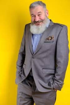 Lustiger bärtiger mann des studioporträts im grauen geschäftsanzug, der kamera, arbeitsberufslebensstil, gelben hintergrund sucht.