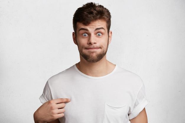 Lustiger bärtiger mann drückt lippen, zeigt auf leeres lässiges t-shirt