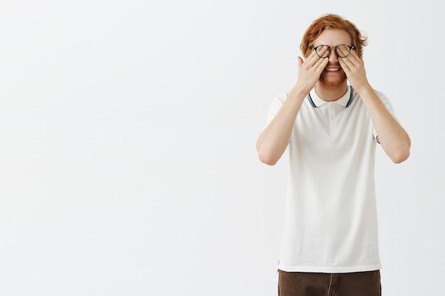 Lustiger bärtiger rothaariger kerl, der mit brille gegen die weiße wand aufwirft