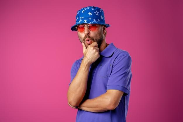 Lustiger bärtiger smiley-mann, der strandhut und sonnenbrille gegen rosa hintergrund trägt