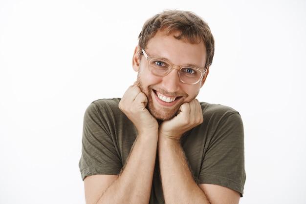 Lustiger berührter und niedlicher erwachsener kaukasischer mann in gläsern mit borsten, die sich auf handflächen stützen und mit mädchenhaftem ausdruck lächeln, der zufrieden und niedlich weiblich handelt