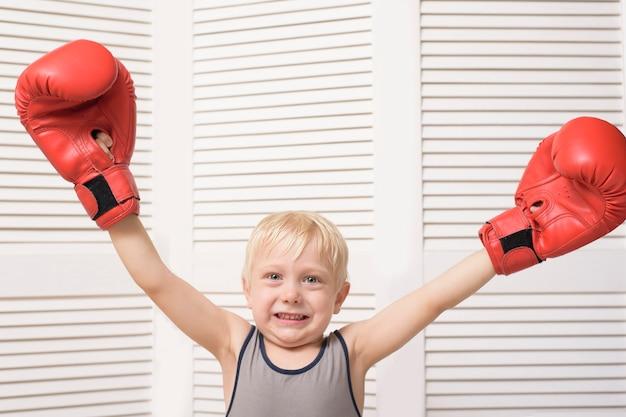 Lustiger blonder junge in den roten boxhandschuhen. sportkonzept