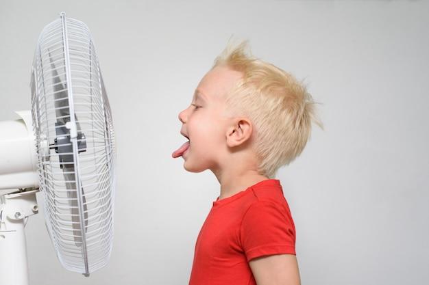 Lustiger blonder junge in einem roten t-shirt nahe dem fan mit seiner zunge, die heraus haftet. genieße kühle luft. sommer