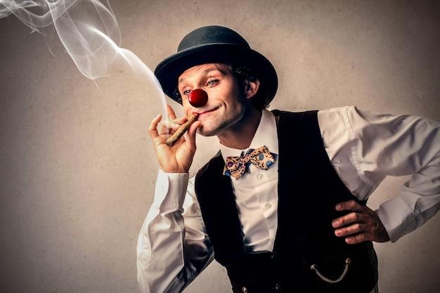 Lustiger clown, der eine zigarre raucht