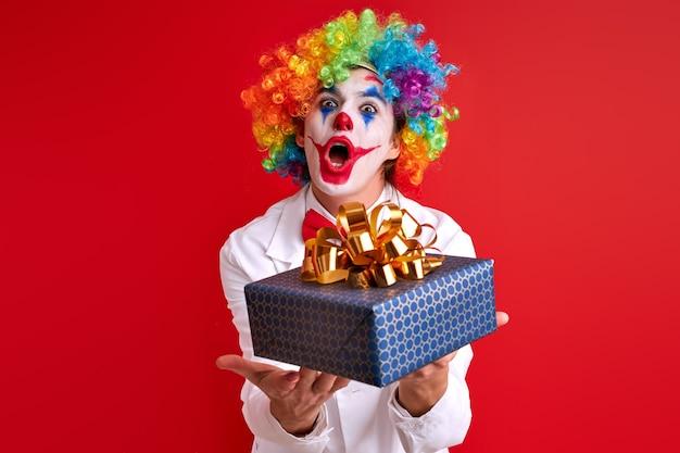Lustiger clown, der geschenkbox in den händen hält, die lokal über roter wand aufwerfen. feier, spiel, kinder, leistungskonzept