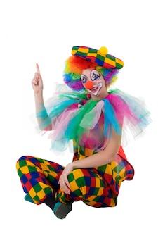 Lustiger clown, der glücklich aufwärts auf kopienraum zeigt