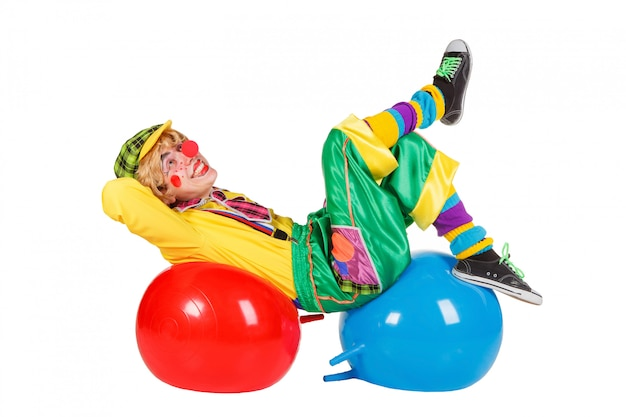 Lustiger clown liegt auf den bällen, die auf weißem hintergrund lokalisiert werden
