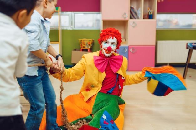 Lustiger clown mit fröhlichen kindern, die zusammen tauziehen spielen. geburtstagsfeier im spielzimmer feiern