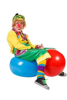 Lustiger clown sitzt auf blauen und roten gummibällen, die auf dem weißen hintergrund isoliert sind