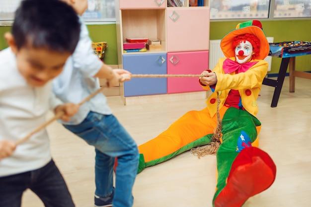 Lustiger clown und fröhliche kleine jungen, die zusammen tauziehen spielen. geburtstagsfeier im spielzimmer feiern