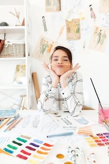 Lustiger damenmodeillustrator, der am tisch sitzt und scherzt