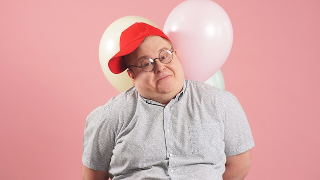 Lustiger dicker mann in einer roten baseballkappe, die luftballons auf einem rosa hintergrund hält