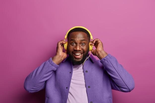 Lustiger dunkelhäutiger bärtiger mann hört musik in kopfhörern von einem modernen gerät, hält die hände auf den ohren, genießt guten klang, hat gute laune