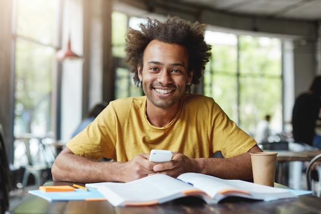 Lustiger dunkelhäutiger mann mit afrikanischer frisur, der auf kurspapier arbeitet, während er während der mittagspause im café sitzt und smartphone hält, das glücklich ist, seine arbeit zu beenden. afrikanischer typ mit breitem lächeln im café
