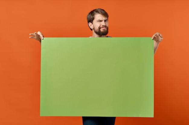 Lustiger emotionaler mann grüner fahnenmodellplakat lokalisierter hintergrund. hochwertiges foto