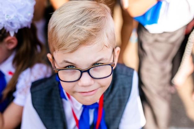 Lustiger entzückender kleiner junge mit brille an seinem ersten tag zur schule oder zum kindergarten.