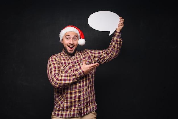 Lustiger ernster mann in der roten weihnachtsmann-weihnachtsmütze hält leeren weißen karton als leer oder verspottet mit kopienraum für text. schwarzer hintergrund